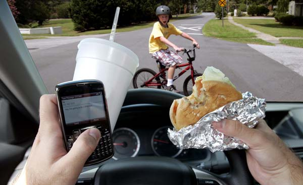 driver distracted by fast food and a cell phone